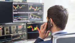 Valutahandlare kollar kurser och talar telefon